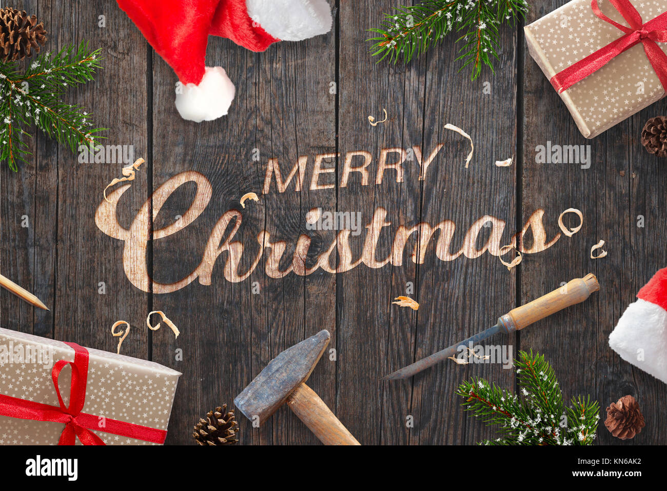 Santa Claus hand carved Merry Christmas text on wooden surface with chisel and hammer. Fir branches, presents and - Stock Image