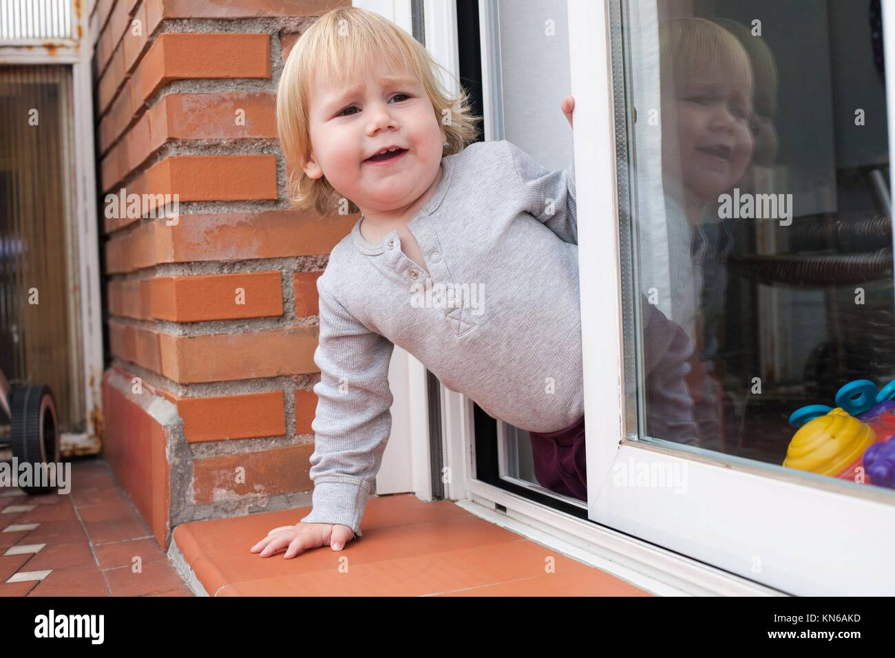 portrait of blonde caucasian baby nineteen month age chubby face calling peering terrace floor supported on the Stock Photo