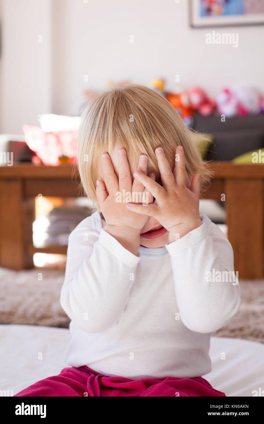 portrait of blonde caucasian baby nineteen month age covering her face with two hands white shirt. Stock Photo