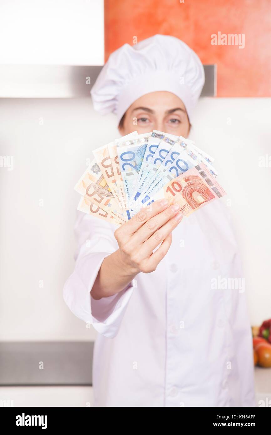 wad of fifty twenty and ten Euro banknotes wad in hands of brunette happy chef woman with professional jacket and - Stock Image