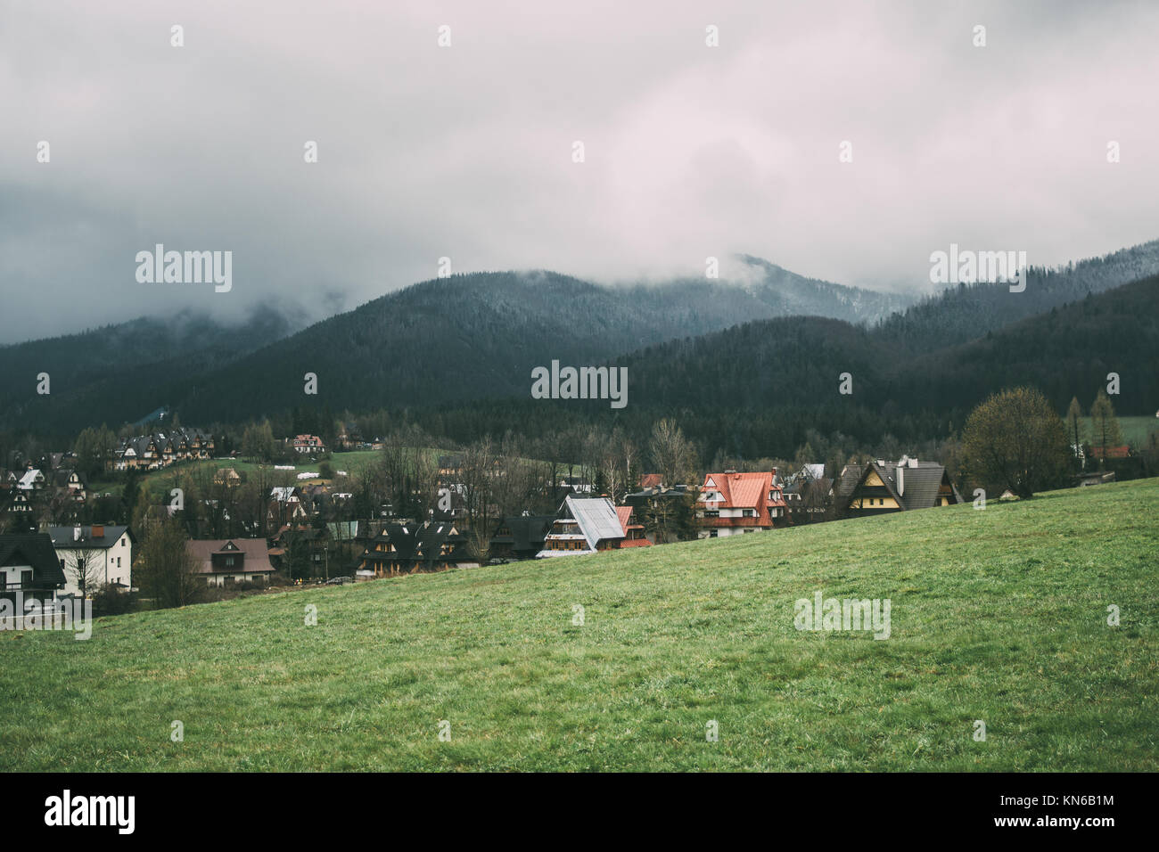 Zakopane in spring with the Tatra mountains covered in clouds on an overcast day - Stock Image