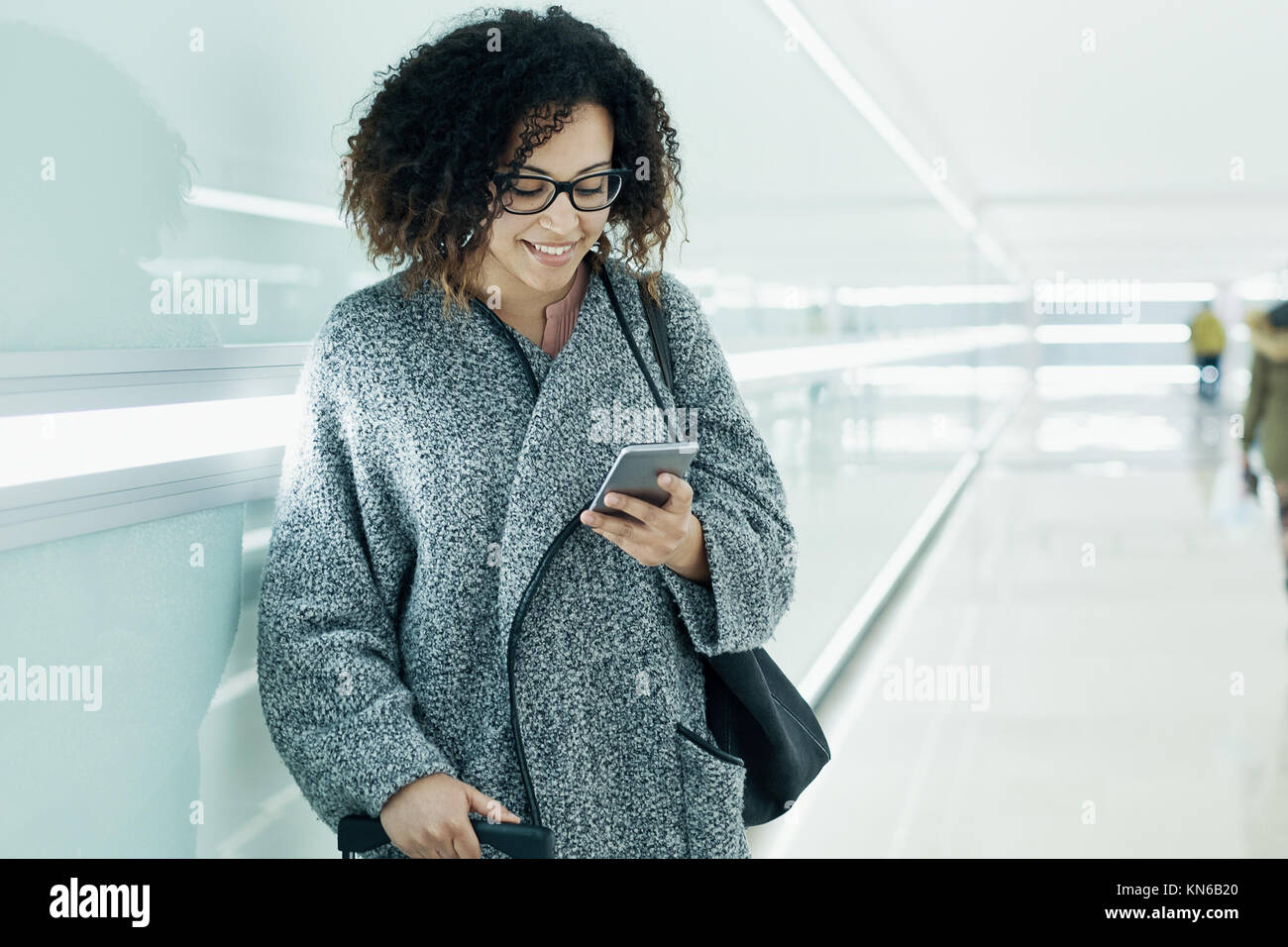 Afro american girl texting and using a smartphone - Stock Image