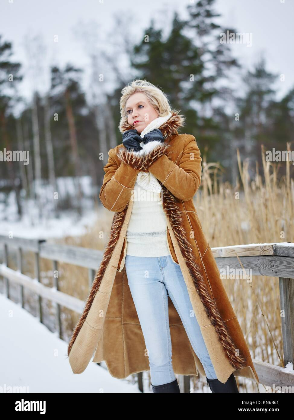 Fashionable mature adult woman wearing winter clothes and she standing next  to the fence - rural scene. South Finland in January. e88f7f05f1b