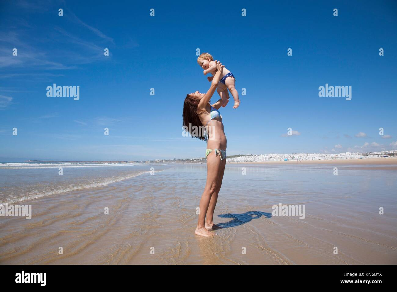 one year baby swimsuit fly in bikini woman mother arms at beach next to Conil Cadiz Spain. - Stock Image