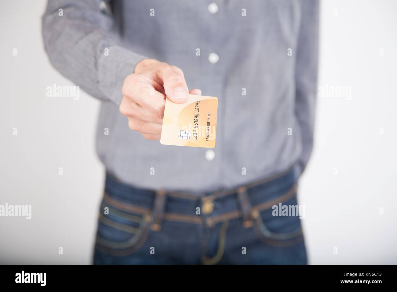 woman blue jeans trousers and grey shirt offering made up fiction credit card in her hands isolated over white background. Stock Photo
