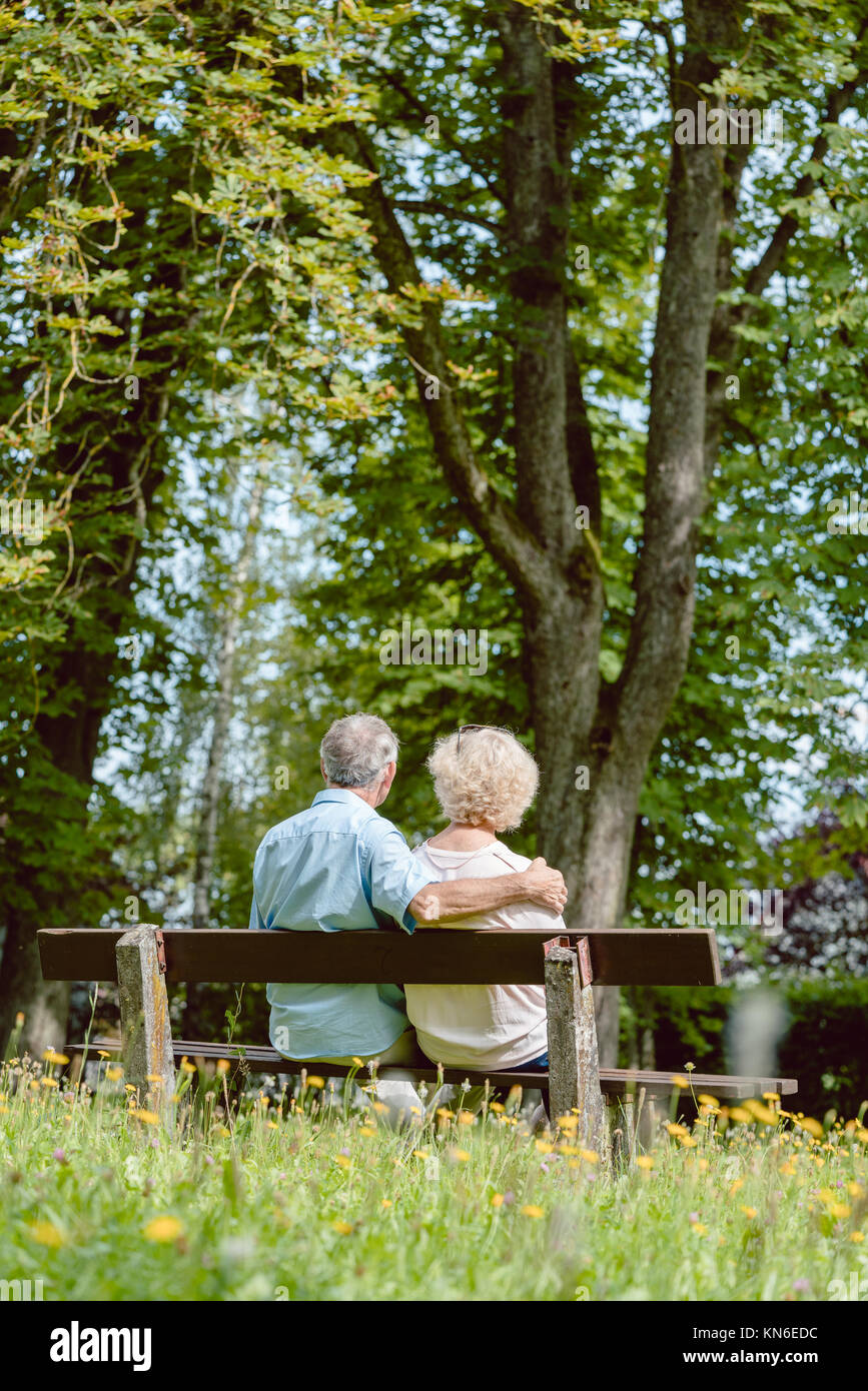 Romantic elderly couple sitting together on a bench in a tranqui - Stock Image