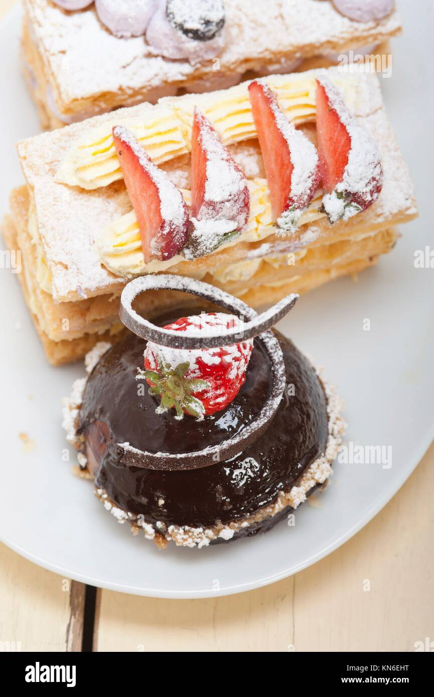 selection of fresh cream napoleon and chocolate mousse cake dessert plate. - Stock Image
