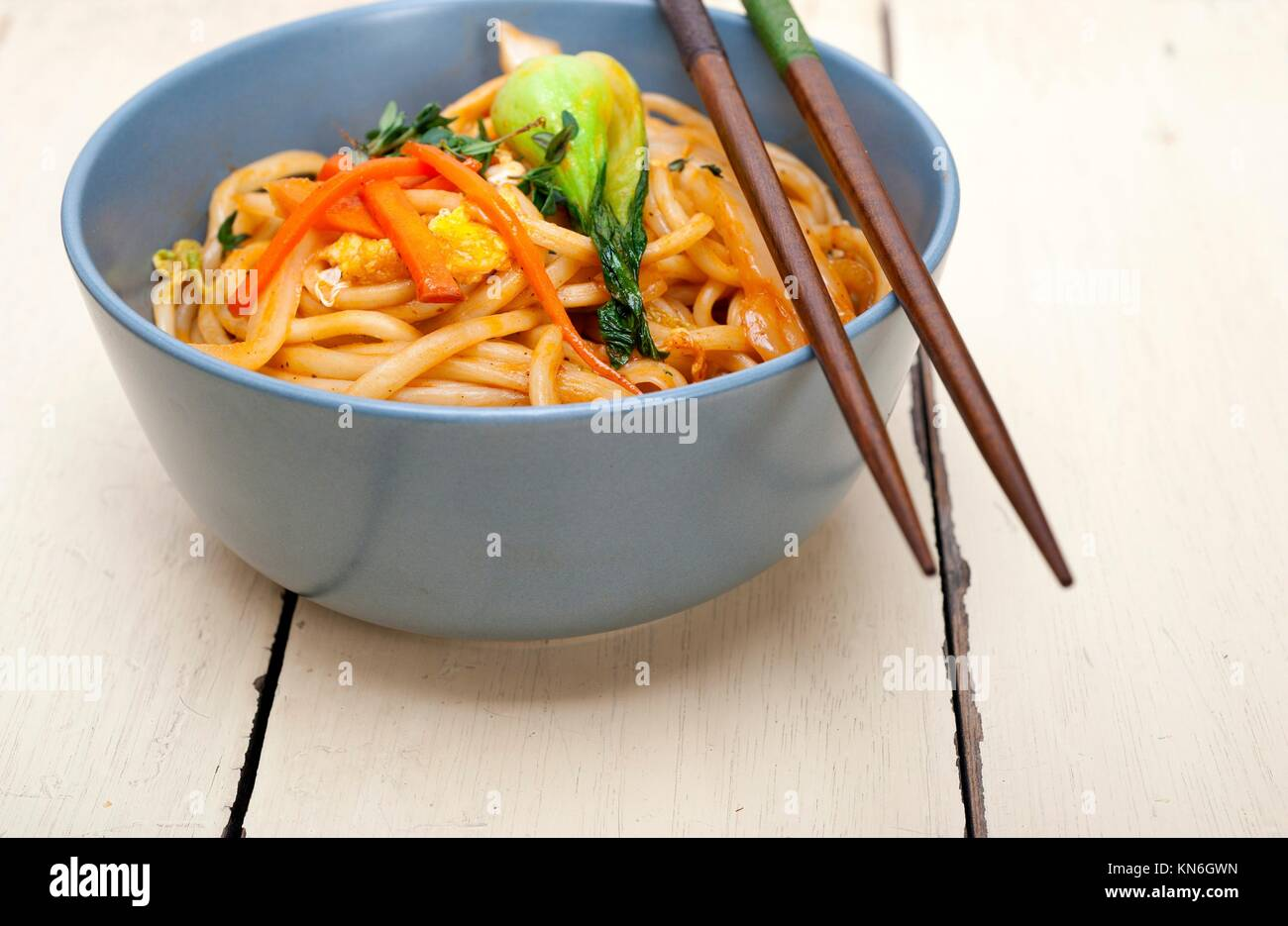 hand pulled stretched Chinese ramen noodles on a bowl with chopstick. - Stock Image