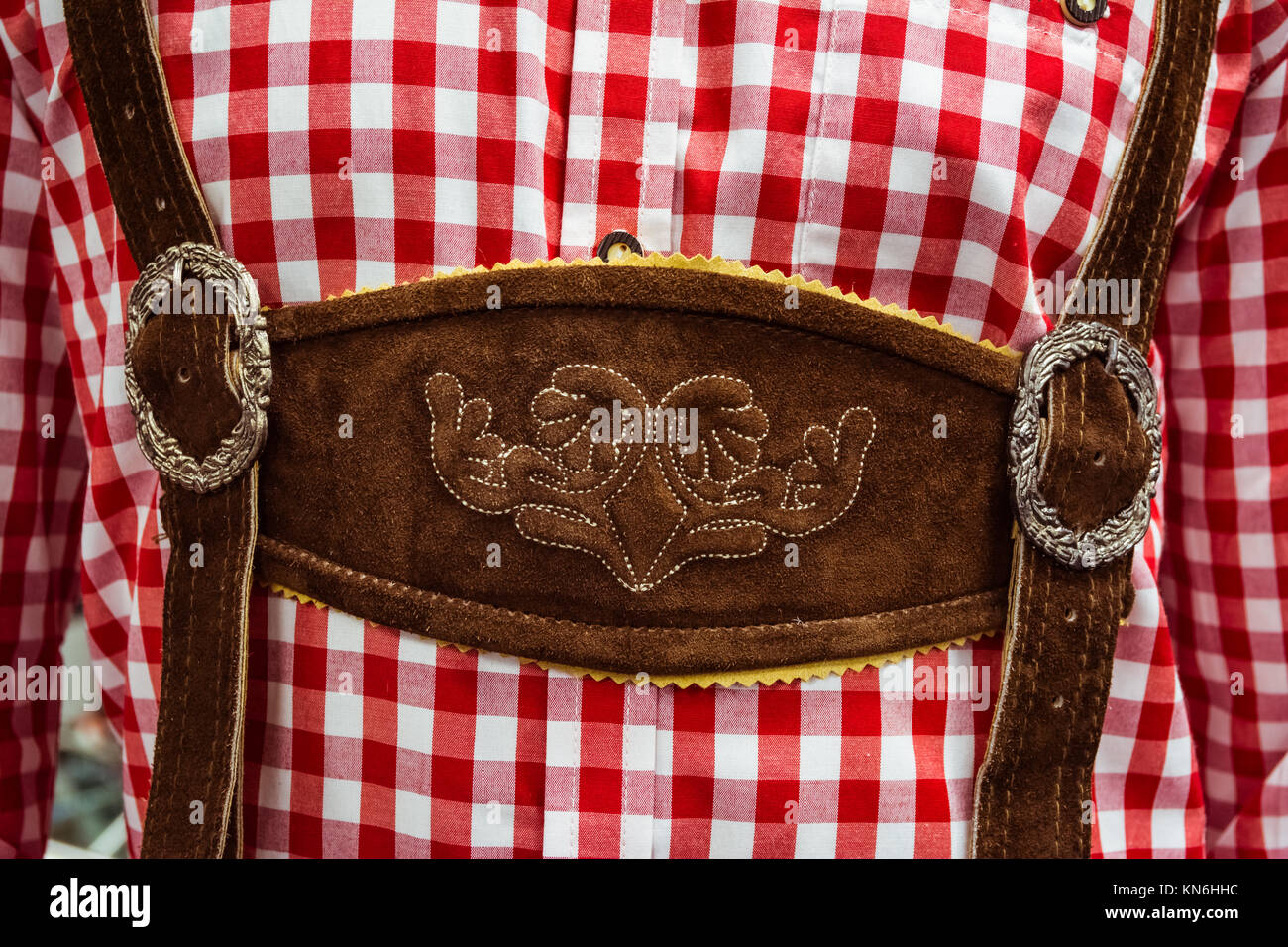 Traditional German Lederhosen Center Chestpiece Closeup Leather Plaid Dress Red White - Stock Image