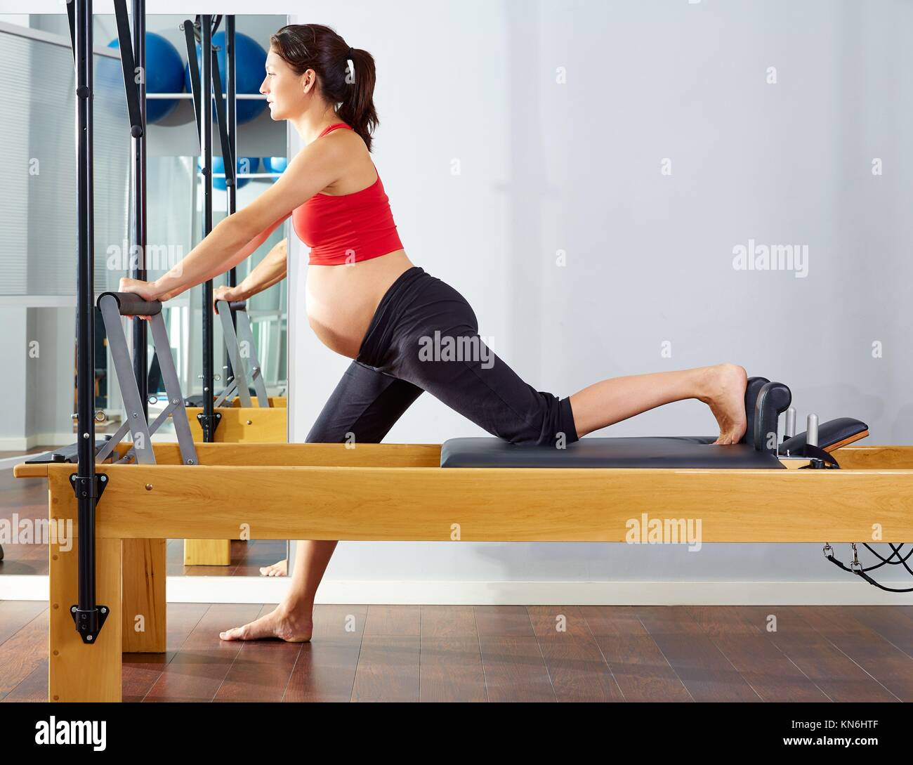 pregnant woman pilates reformer cadillac exercise workout at gym. - Stock Image