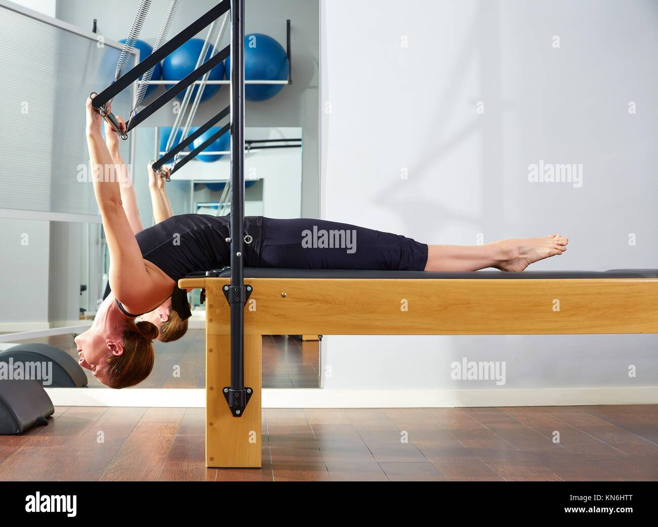 Pilates woman in reformer exercise at gym indoor. - Stock Image