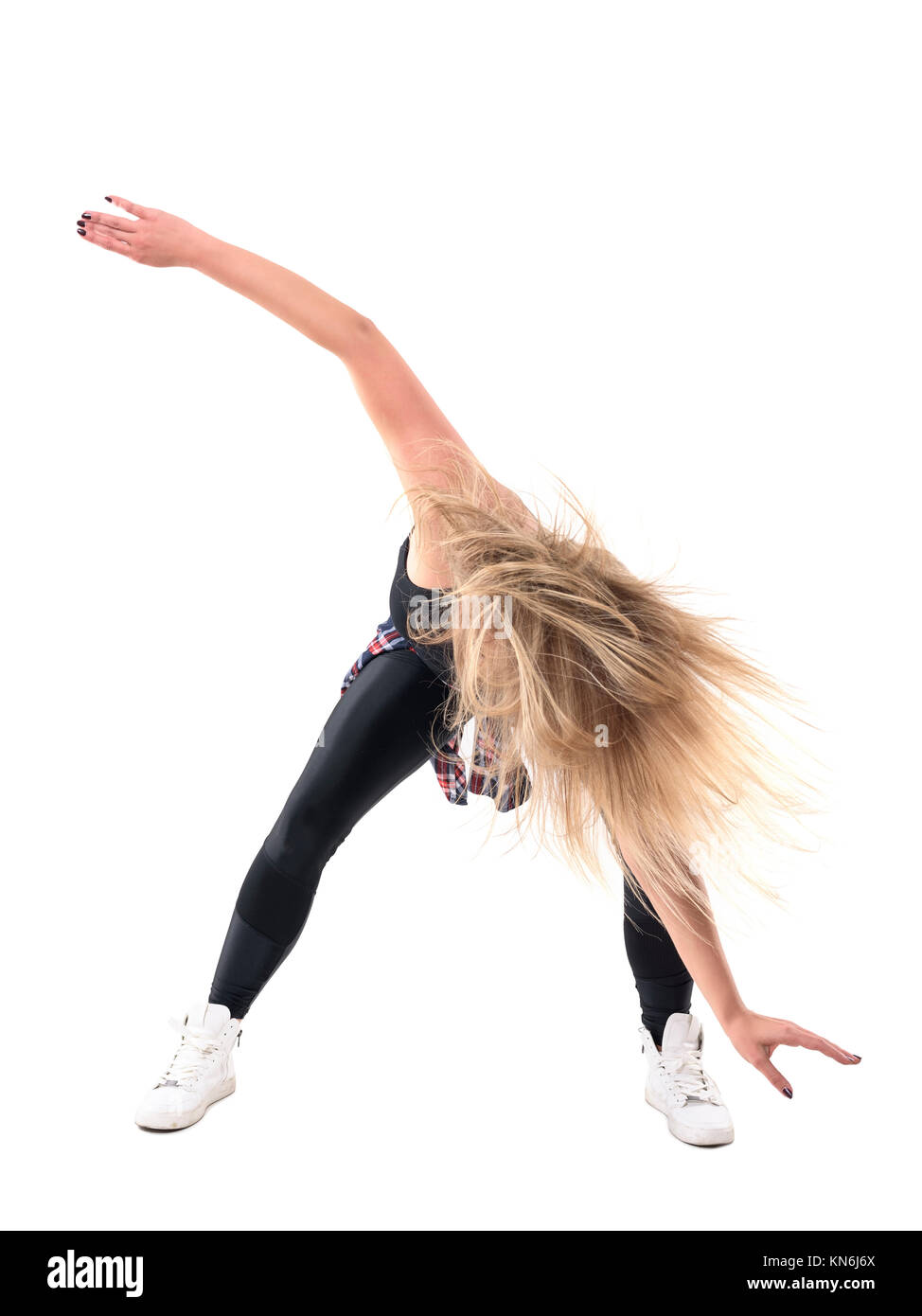 Action motion of bent woman aerobics instructor dancing jazz dance with flowing tousled hair. Full body length portrait - Stock Image
