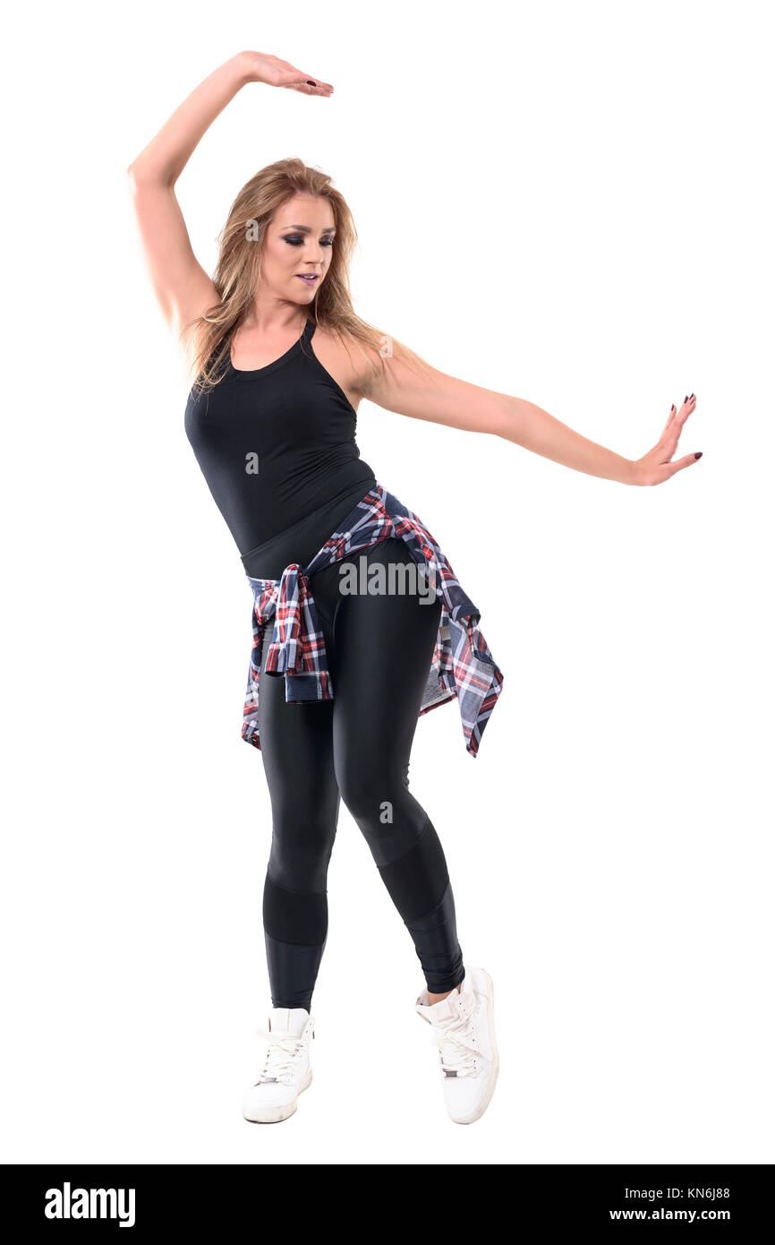 Posture of young attractive woman dancer swinging arms and dancing aerobics joyfully. Full body length portrait - Stock Image
