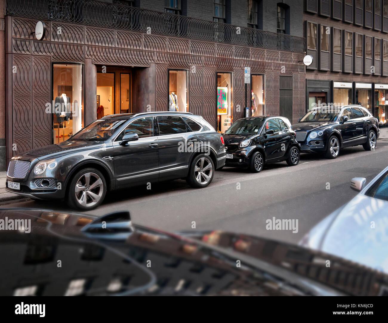 Bentley Bentayga's with Smart car parked in Albemarle Street London UK - Stock Image