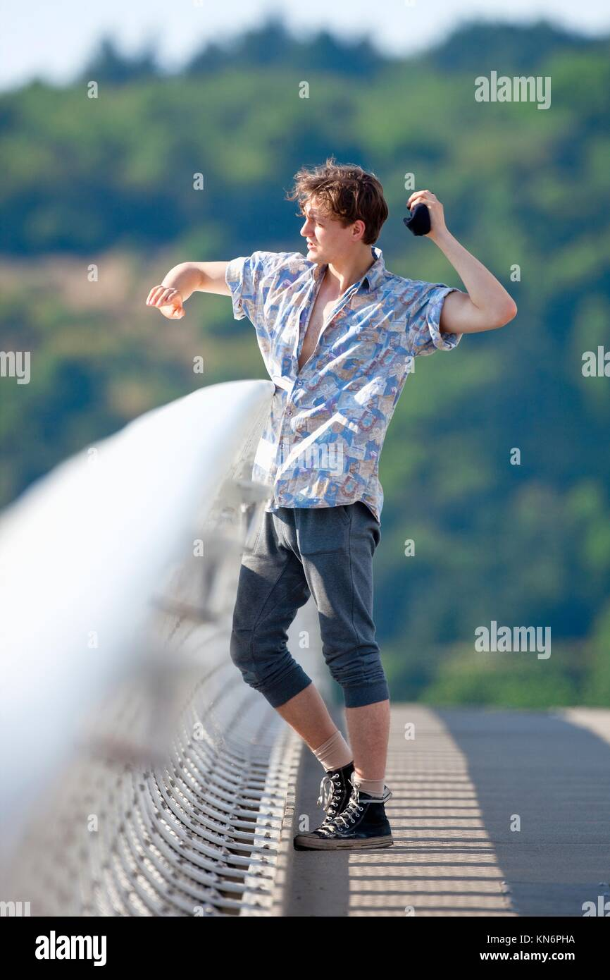 Young Man Standing on the Bridge Throwing Down Something. - Stock Image