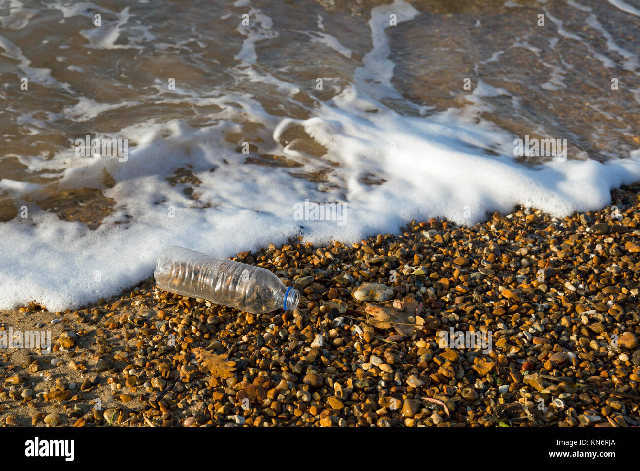 A clear plastic empty 500ml bottle on a shingle beach with waves lapping around it. - Stock Image
