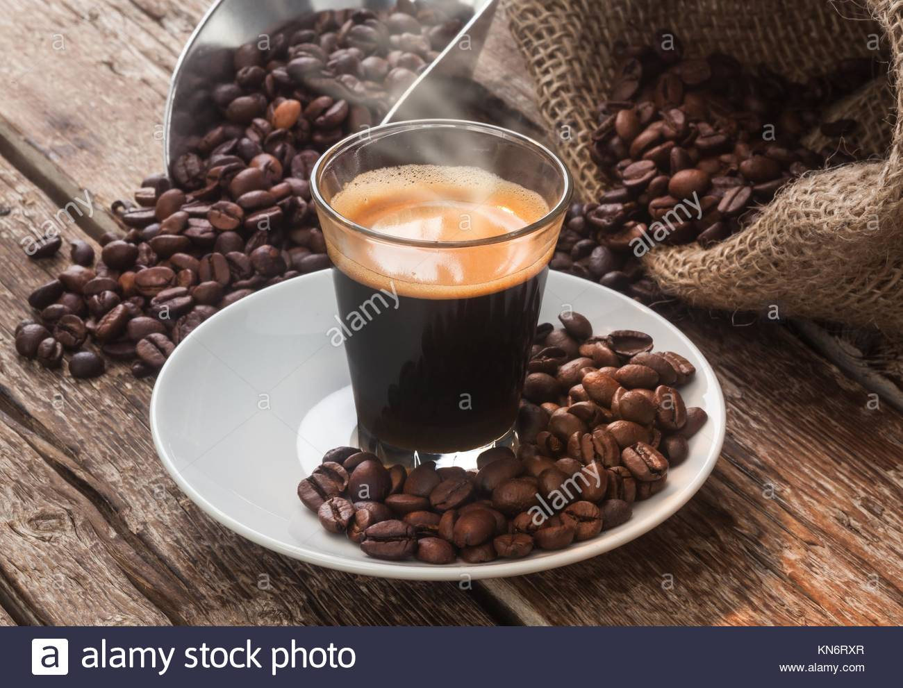 Espresso coffee in glass cup with coffee beans on wooden table. Stock Photo