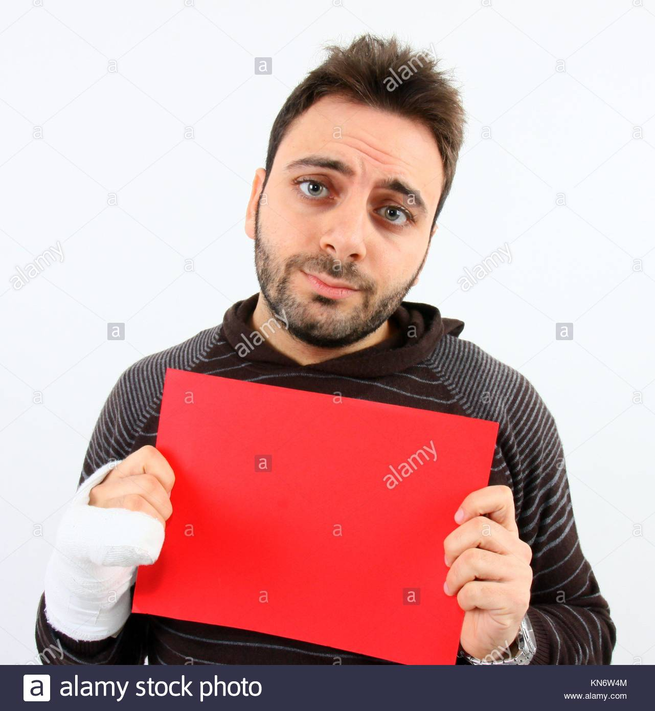 Young man with a fracture of the fifth metacarpal while keeps red billboard. - Stock Image