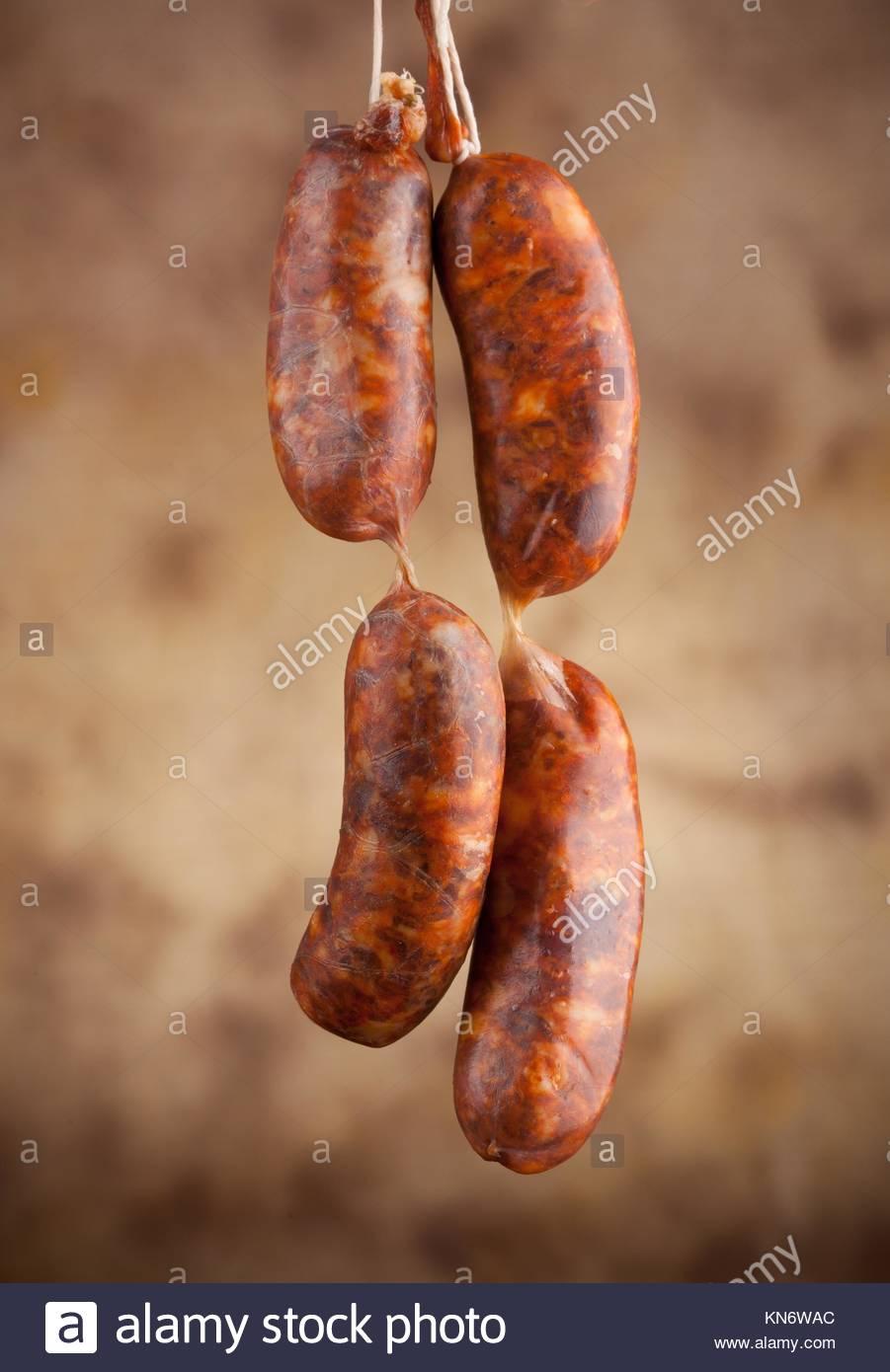 Raw sausage on beige background. - Stock Image