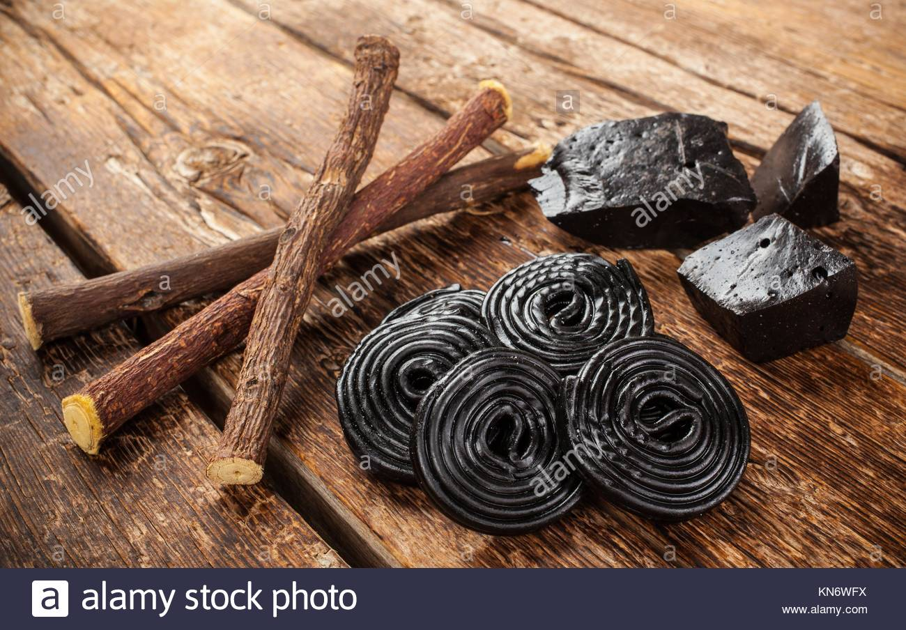 Production steps of licorice, roots, pure blocks and candy on wooden table. - Stock Image