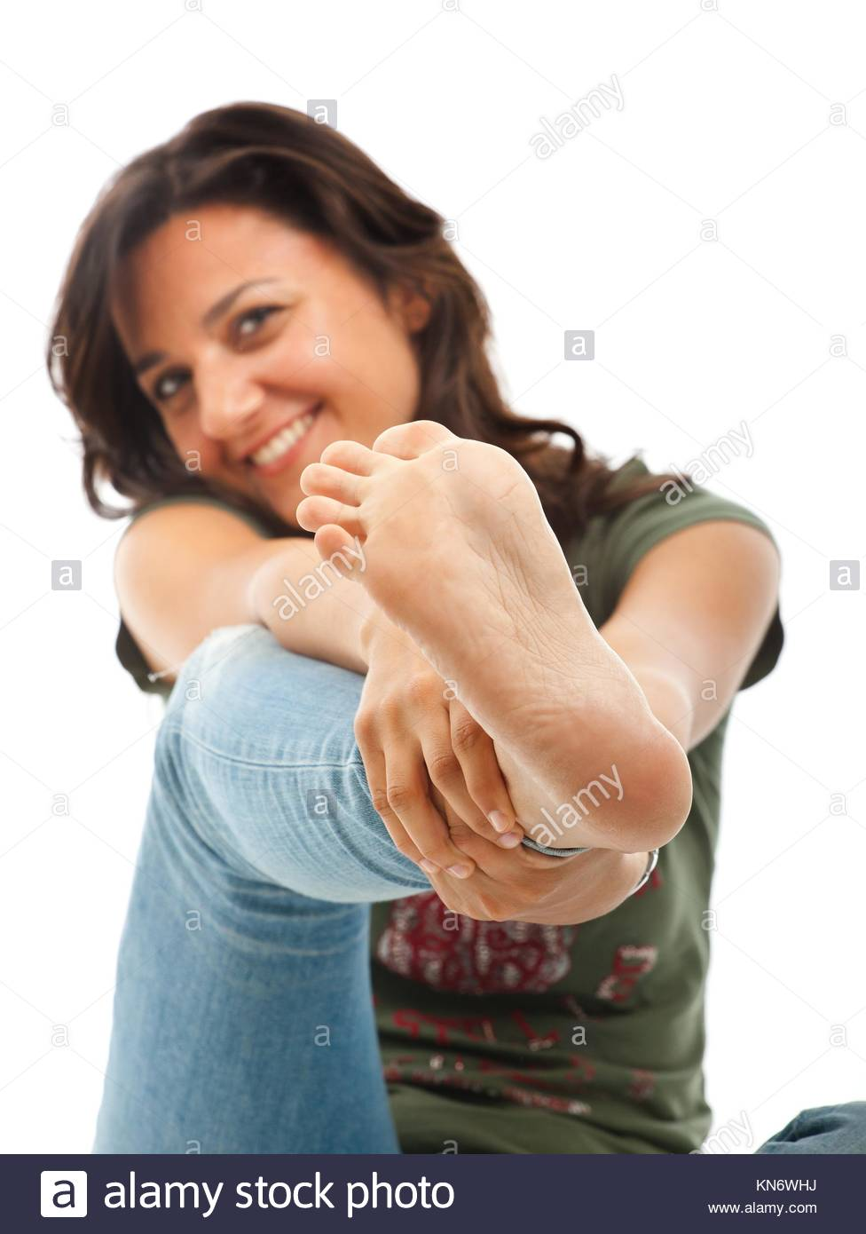 Smiling girl in jeans showing the sole of the foot. - Stock Image