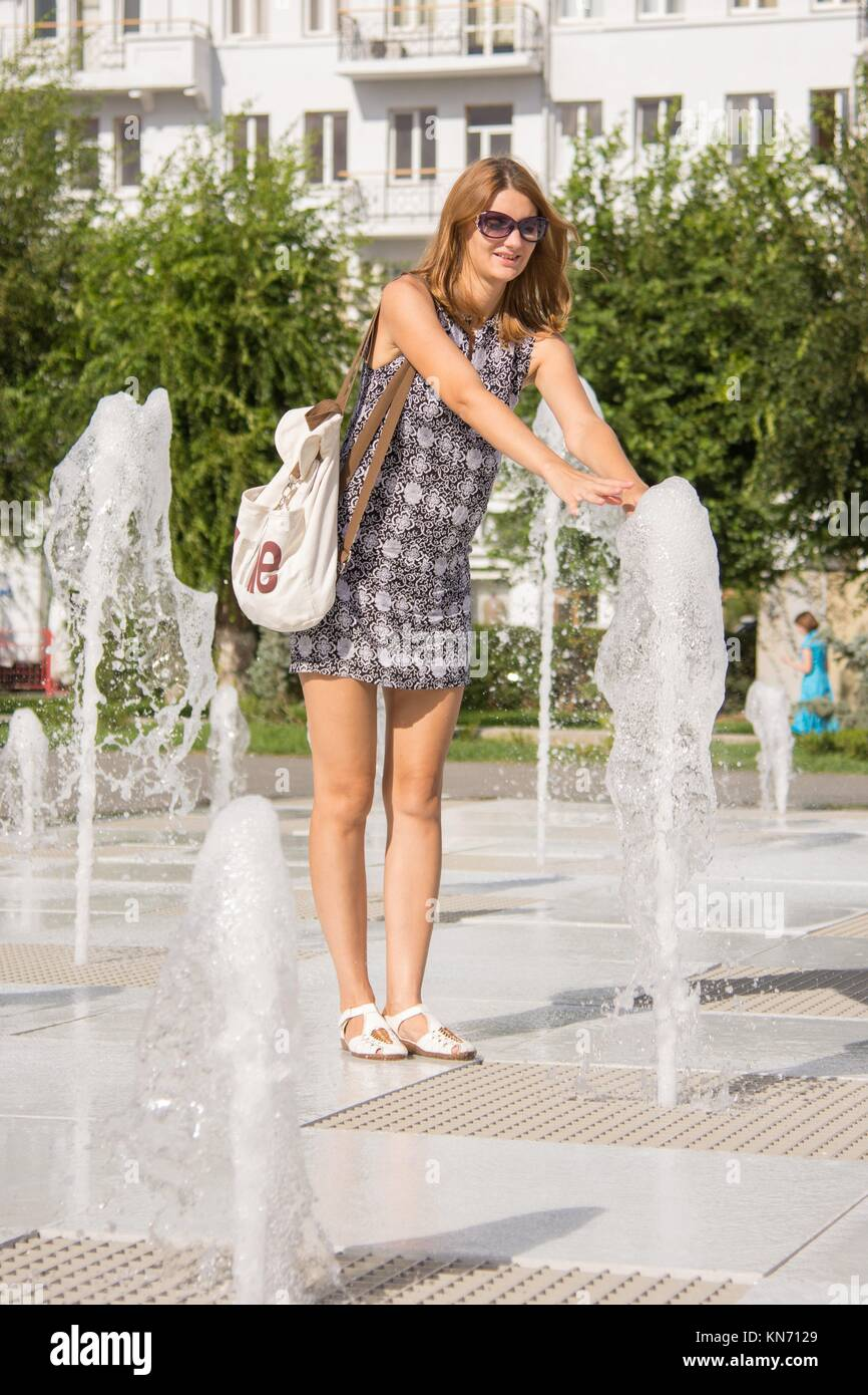 The young girl went to the center of the fountain rises from the earth and touched his hands to the jet fountain. - Stock Image