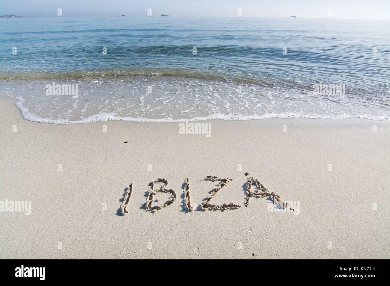 Ibiza written in sand on beach with wave in Ibiza, Balearic islands, Spain. - Stock Image