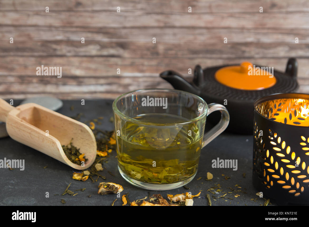 hot green tea in cup composition with candle and tea pot - Stock Image