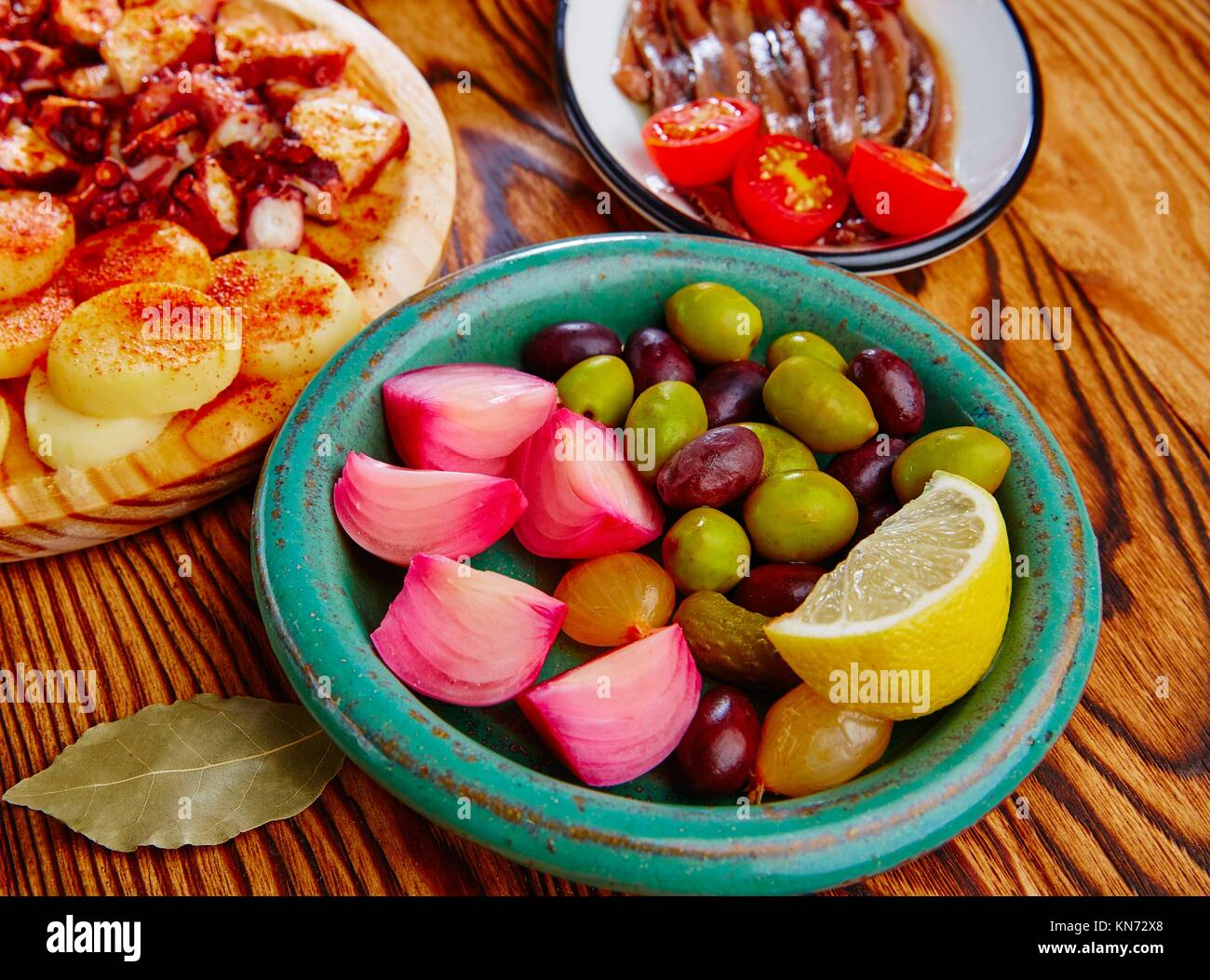 Olives and onion pickles tapas with anchovies and octopus gallega. - Stock Image