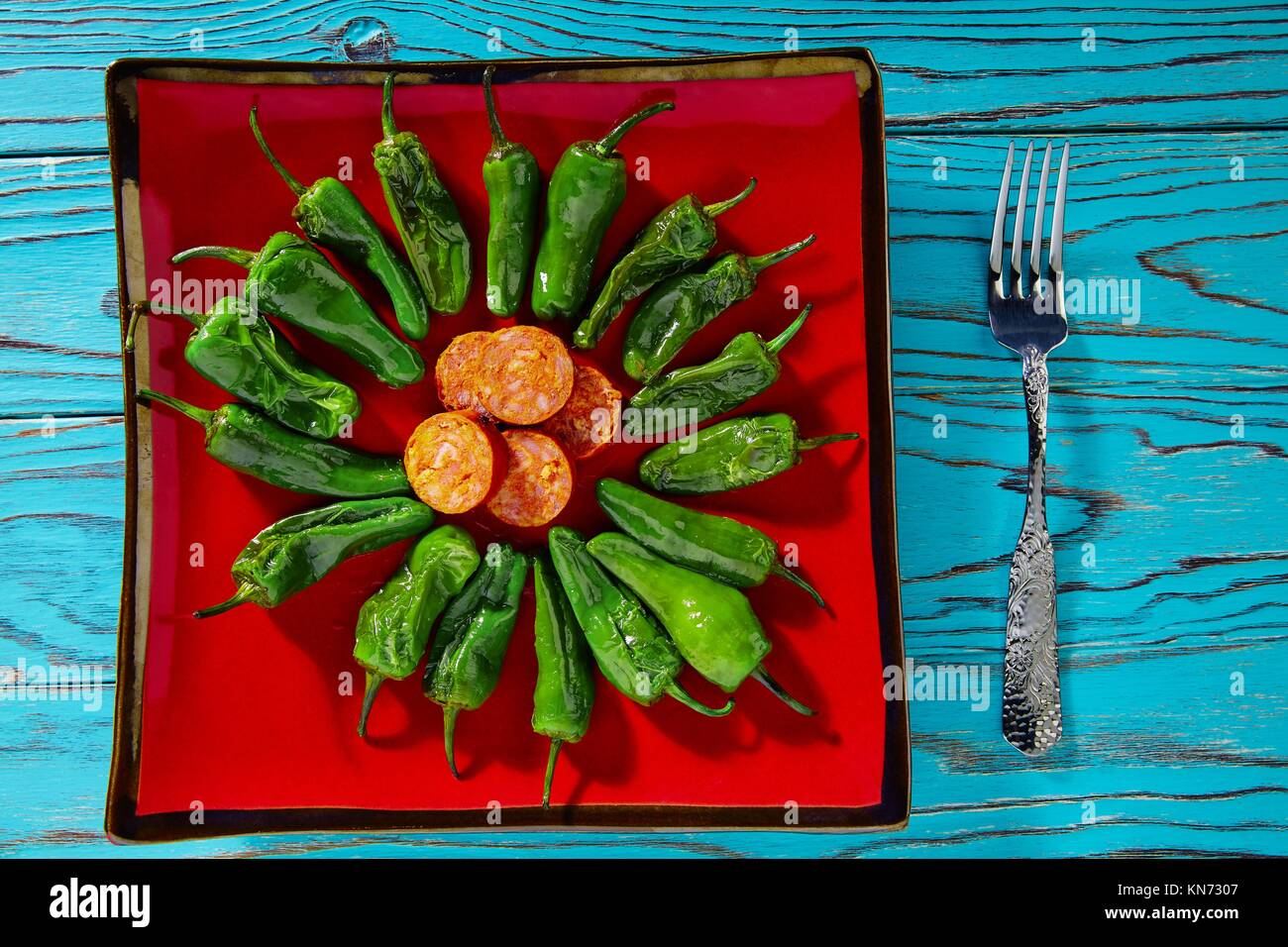 Tapas pimientos del Padron green peppers with sausage. - Stock Image