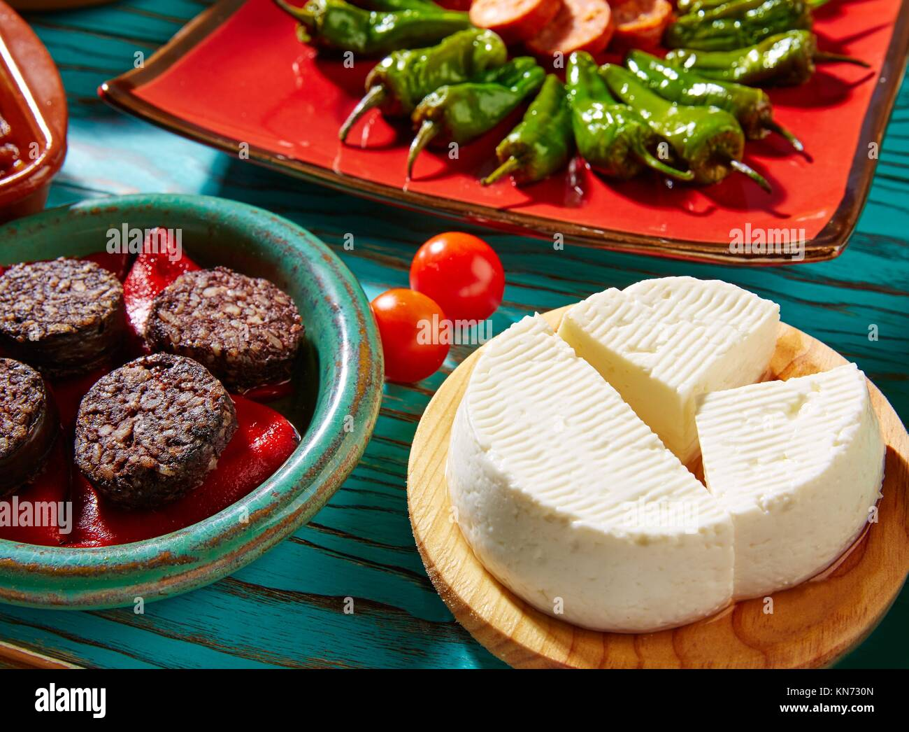 Tapas Morcilla and cheese de Burgos from Spain and padron peppers. - Stock Image