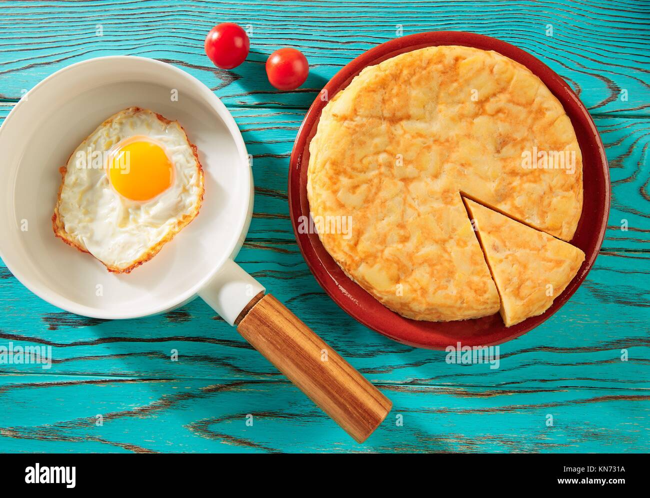 Egg over easy on white pan and potatoes omelette tapas from Spain. - Stock Image