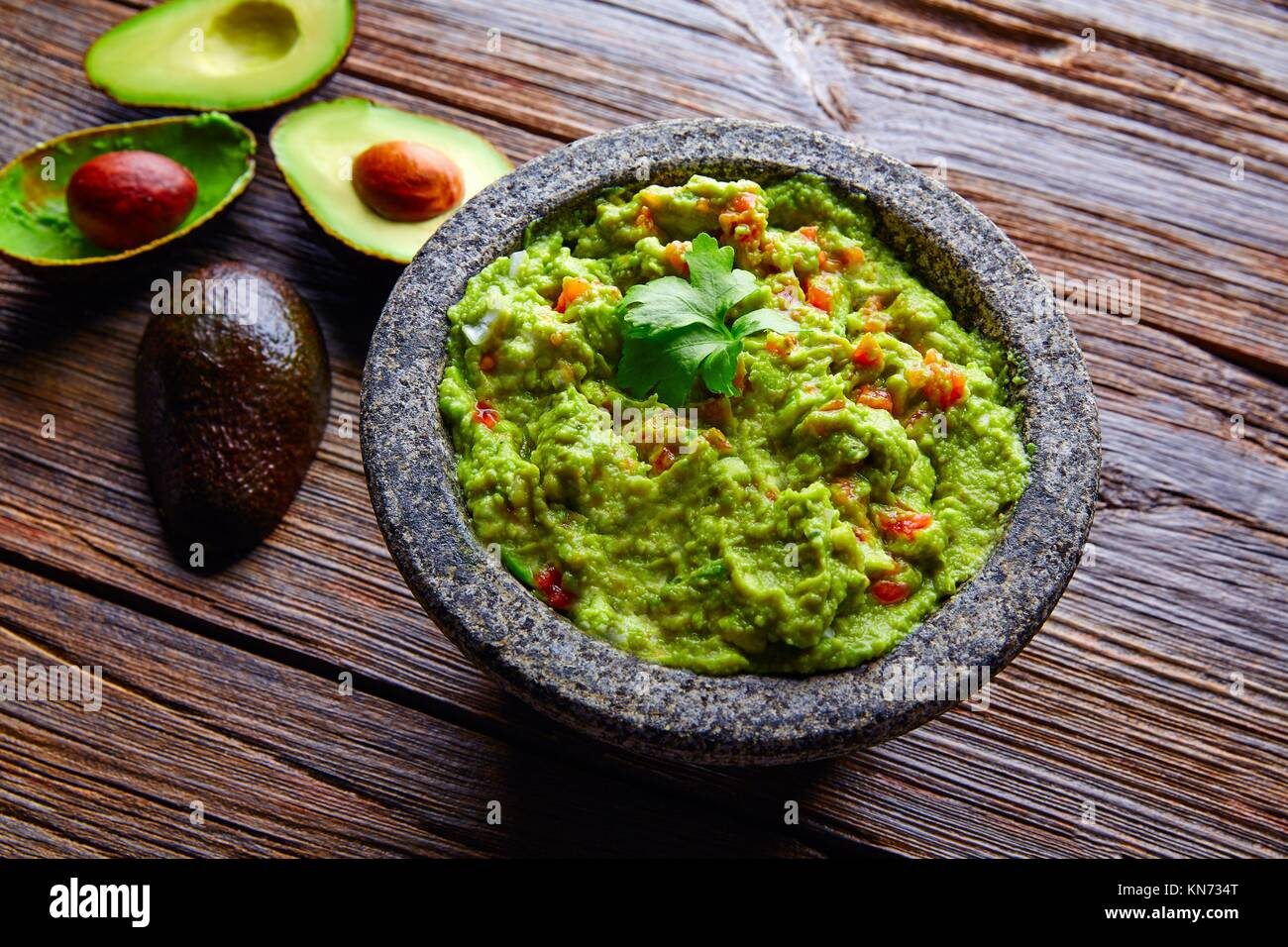 avocado Guacamole on molcajete real Mexican traditional procedure. - Stock Image