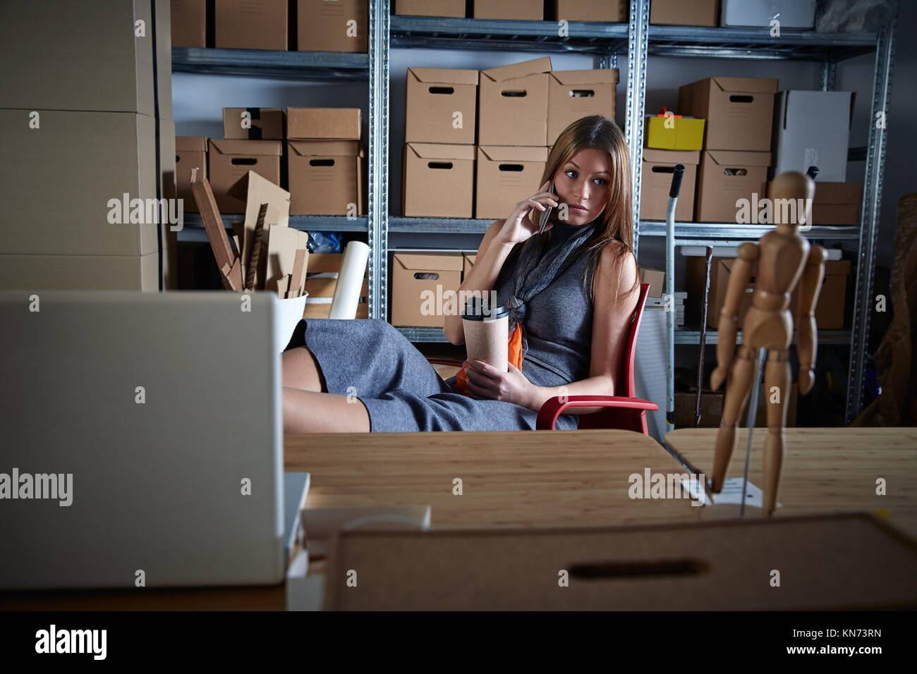 Businesswoman in office warehouse having coffee talking mobile phone relaxed. - Stock Image