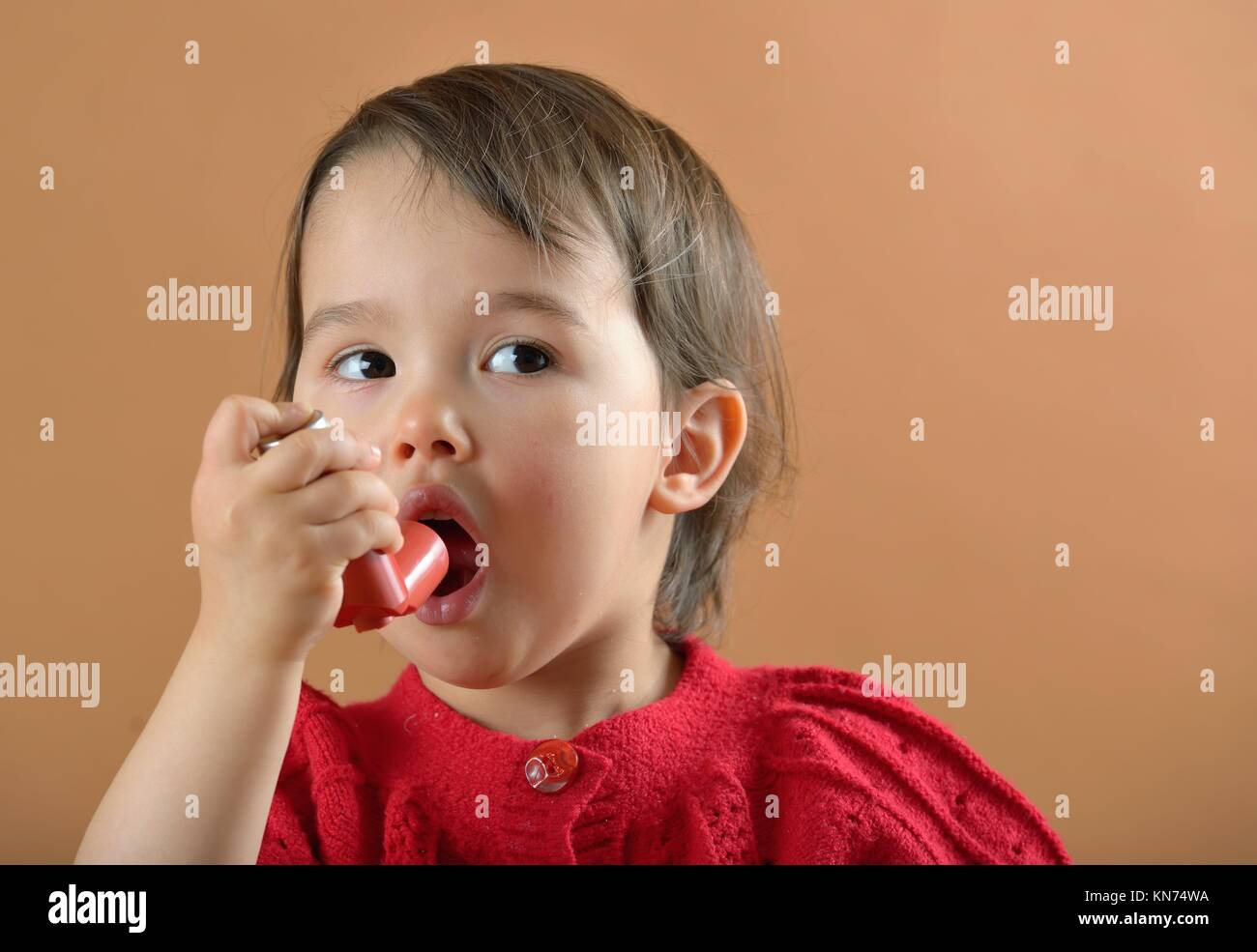 Little girl breathing asthmatic inhaler. - Stock Image