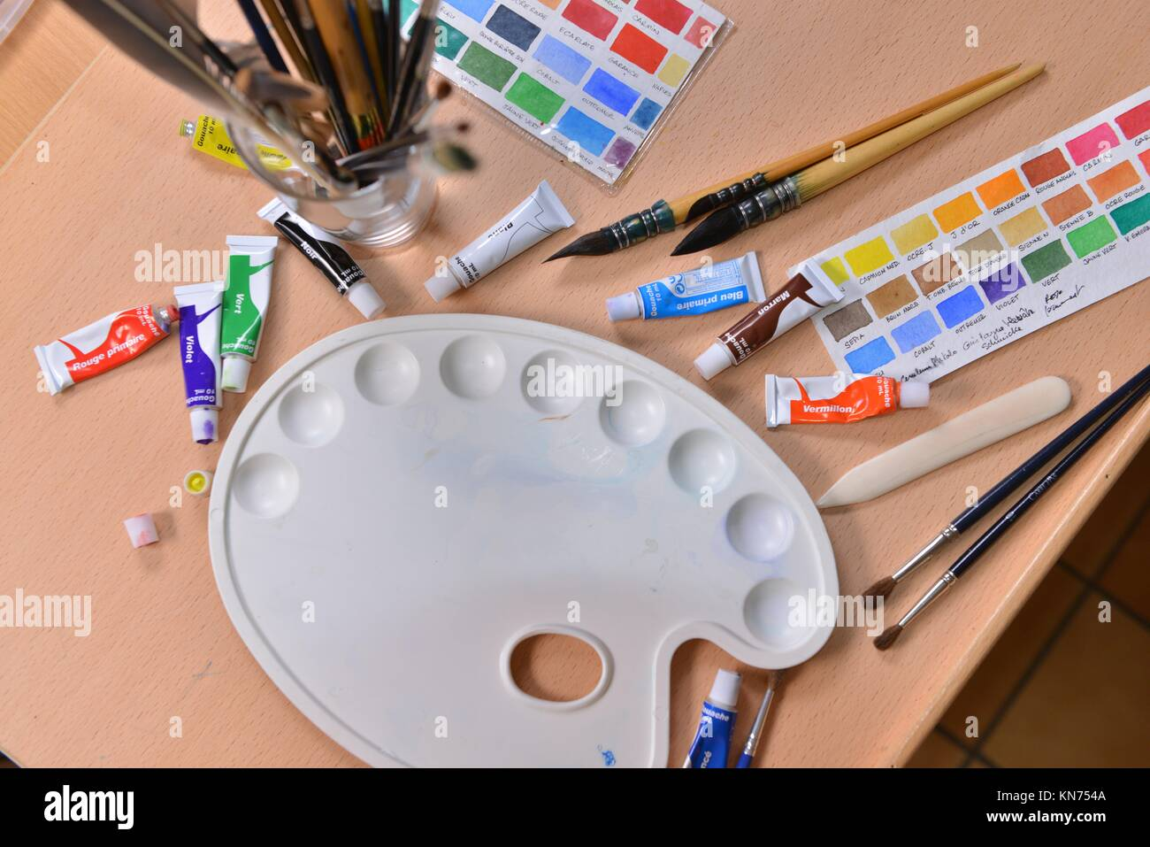 Artist's hand applying paint gouache on the drawing sheet. - Stock Image