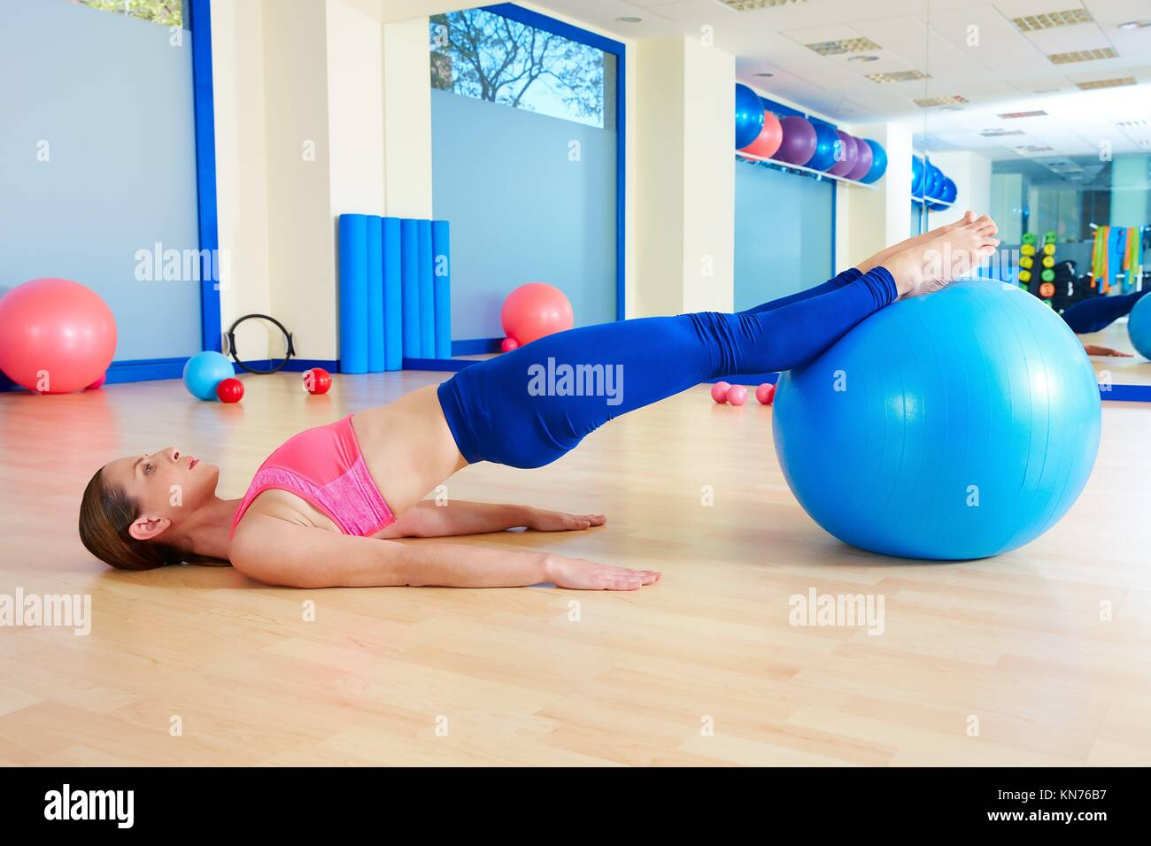 Pilates woman pelvic lift fitball exercise workout at gym indoor swiss ball. - Stock Image