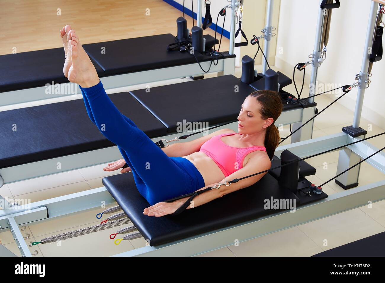 Pilates reformer woman hundred exercise workout at gym indoor. - Stock Image