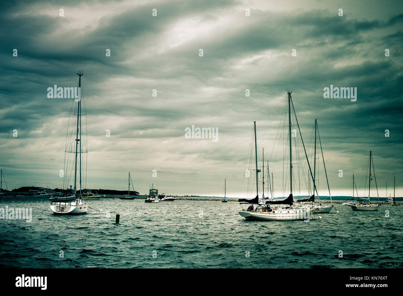 Nautical scene of anchored sailboats under storm clouds - Stock Image
