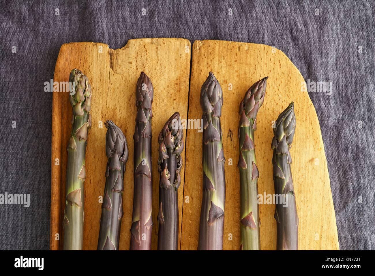 Fresh purple asparagus on vintage wooden baord on linen in dark moody light. - Stock Image