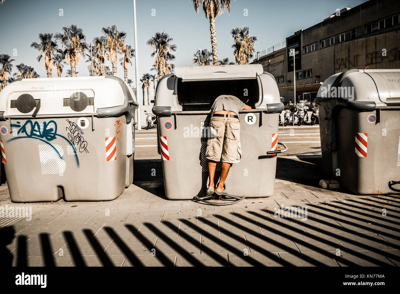 A person looking for something in the garbage of the city of Barcelona. The crisis has caused millions of unemployed - Stock Image