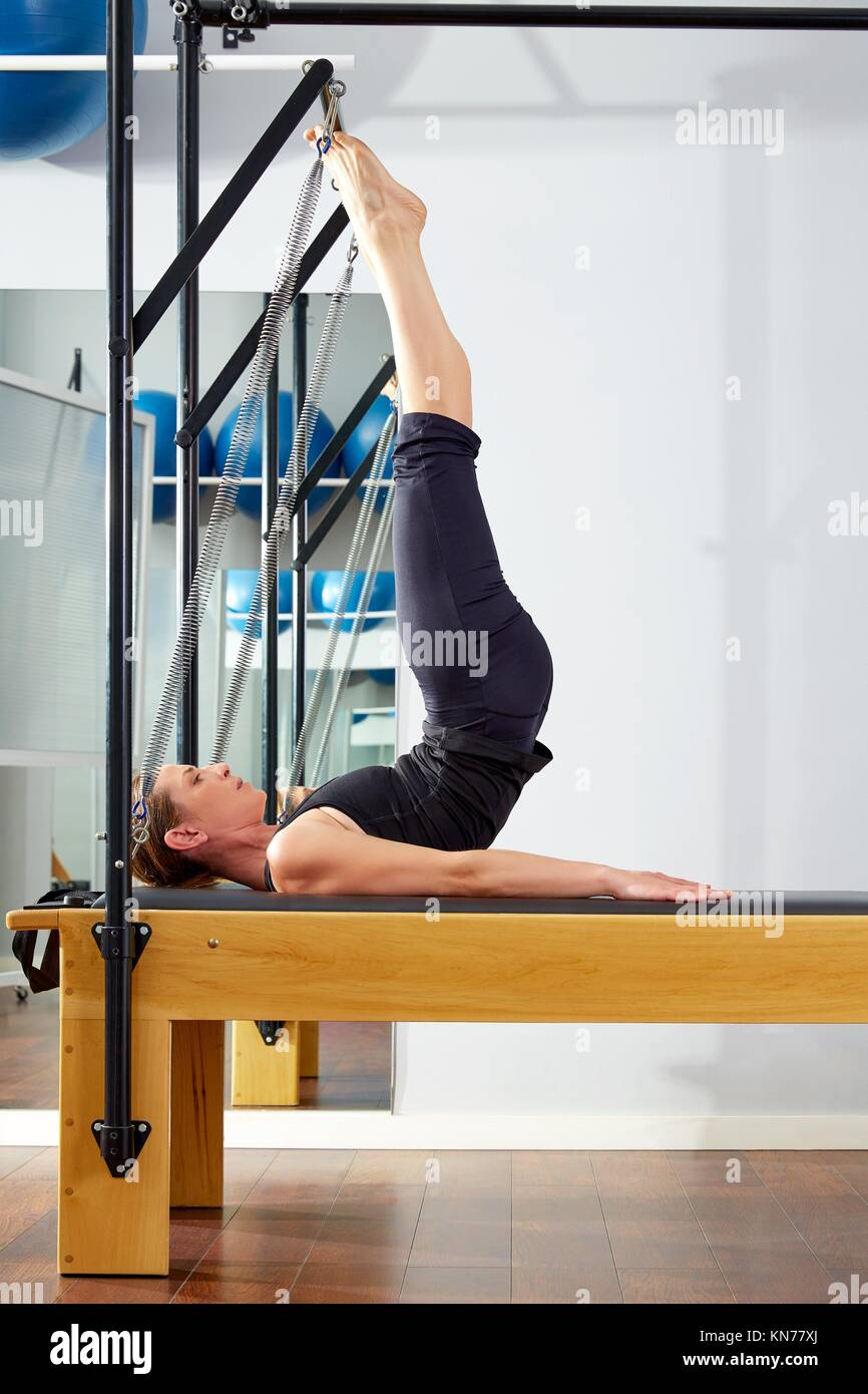 Pilates woman in reformer tower exercise at gym indoor. - Stock Image