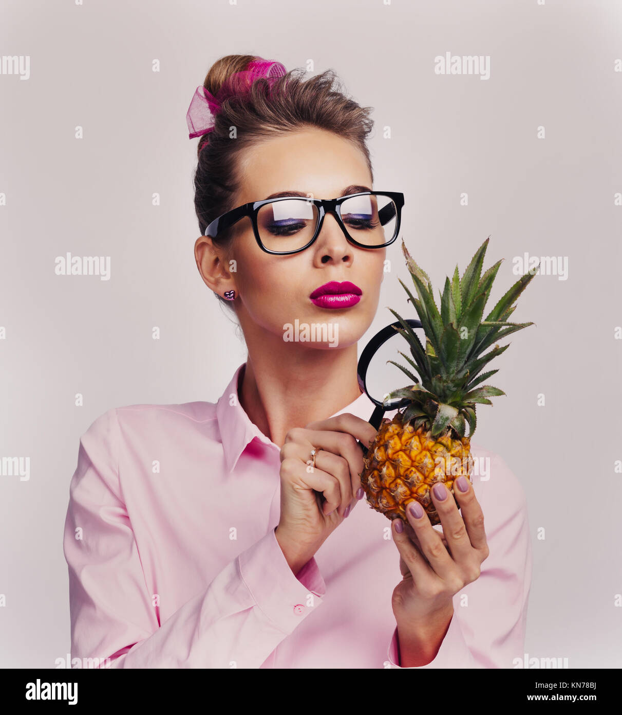 Blonde woman in glasses holding pineapple and llok at it through magnifying glass investigating quality and usefulness - Stock Image