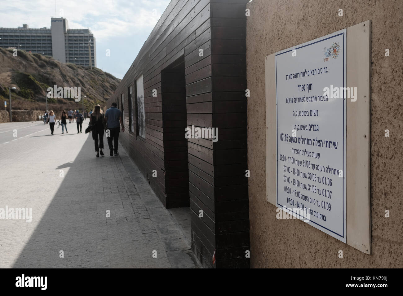 A sign in Hebrew details the times for men and women in a gender segregated beach in Tel Aviv. - Stock Image