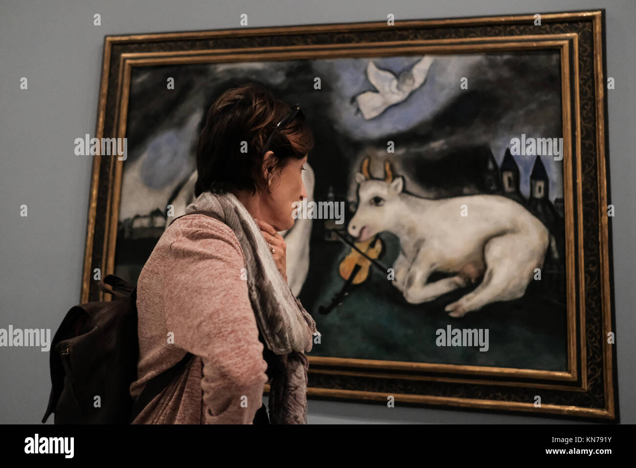 A woman studies a painting by Marc Chagall, on display in the Tel Aviv Museum of Art. - Stock Image