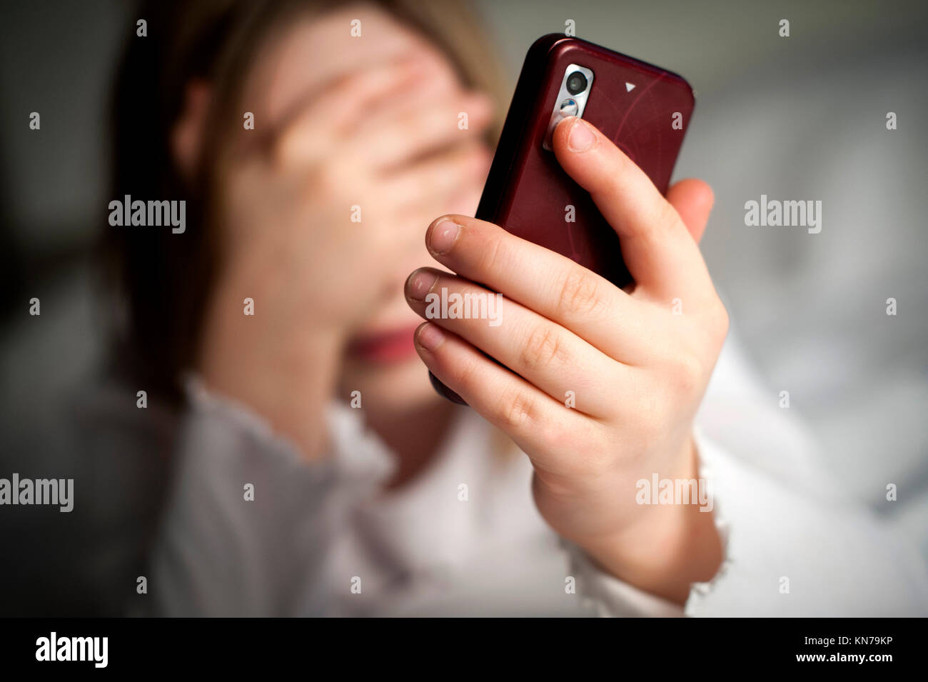 Bad news for a young girl using a smart phone on social media. - Stock Image