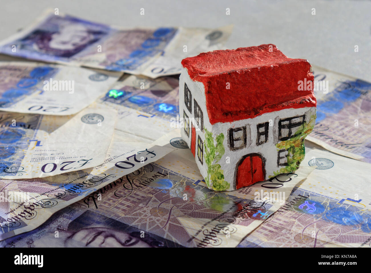 Hand painted stone house sitting on twenty pound notes British currency suggesting savings on stamp duty - Stock Image
