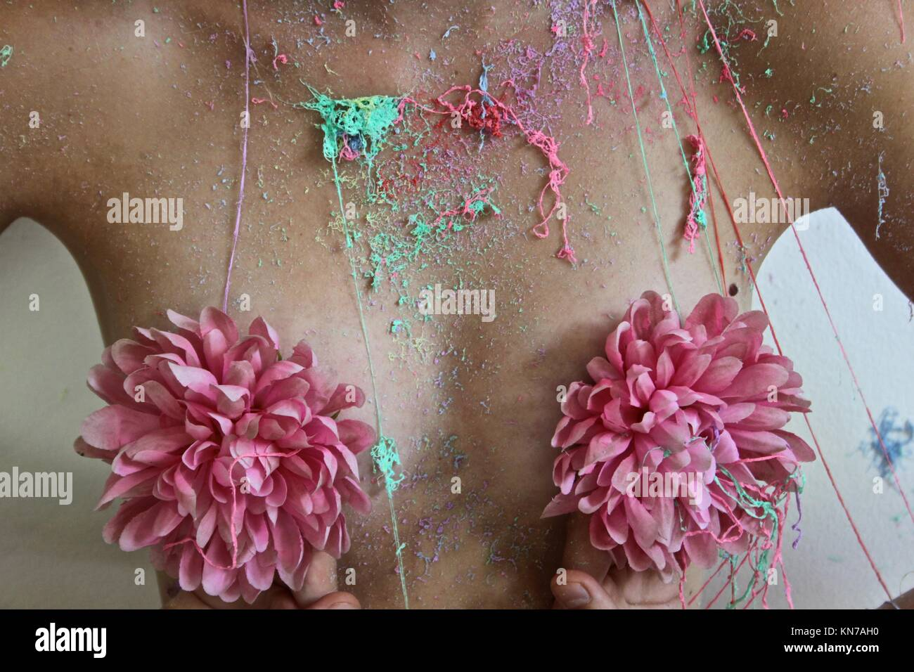 Covered her body with colorful party spray - Stock Image