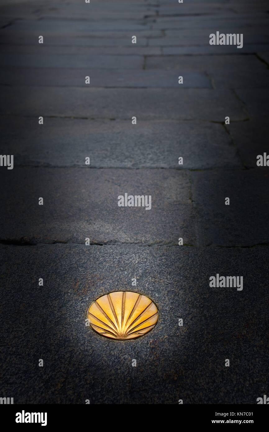 Santiago de Compostela end of Saint James Way golden shell sign on soil in Galicia Spain. - Stock Image