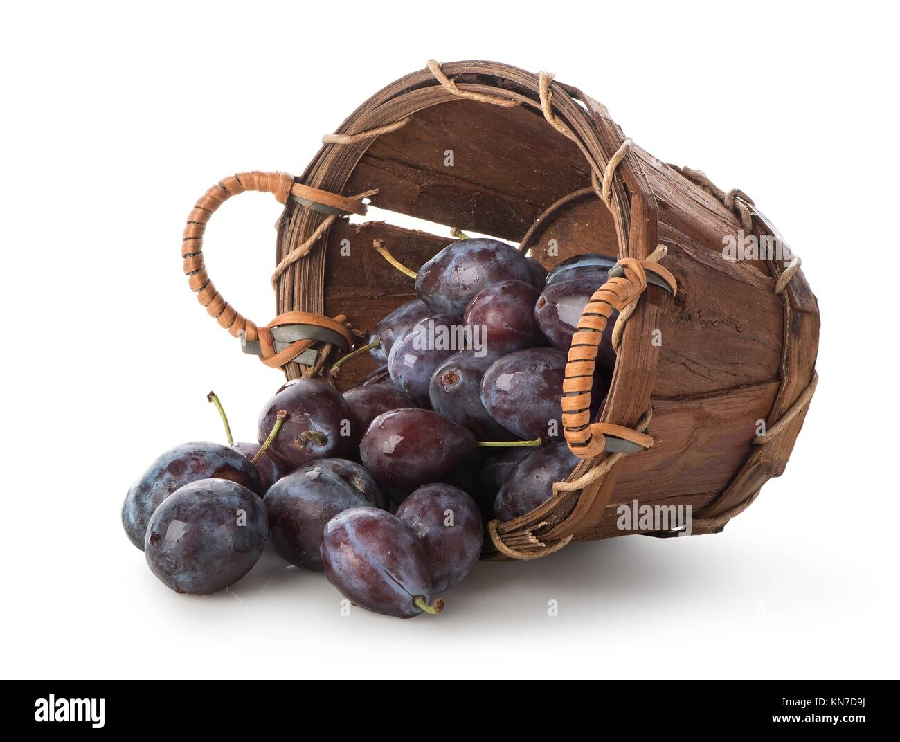 Plums in a basket isolated on white. Stock Photo